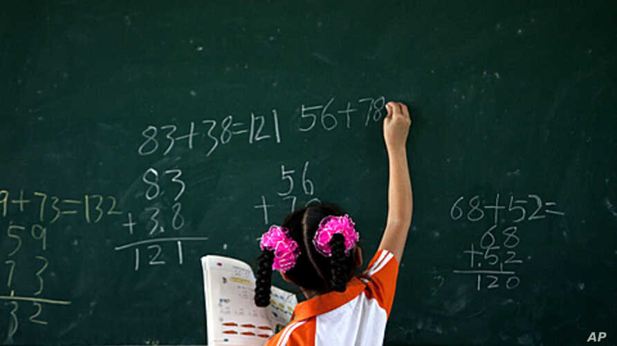 A girl writes on a chalkboard during a math class at Dongba Experimental School, a school for the children of migrant workers, in Beijing, August 25, 2011.