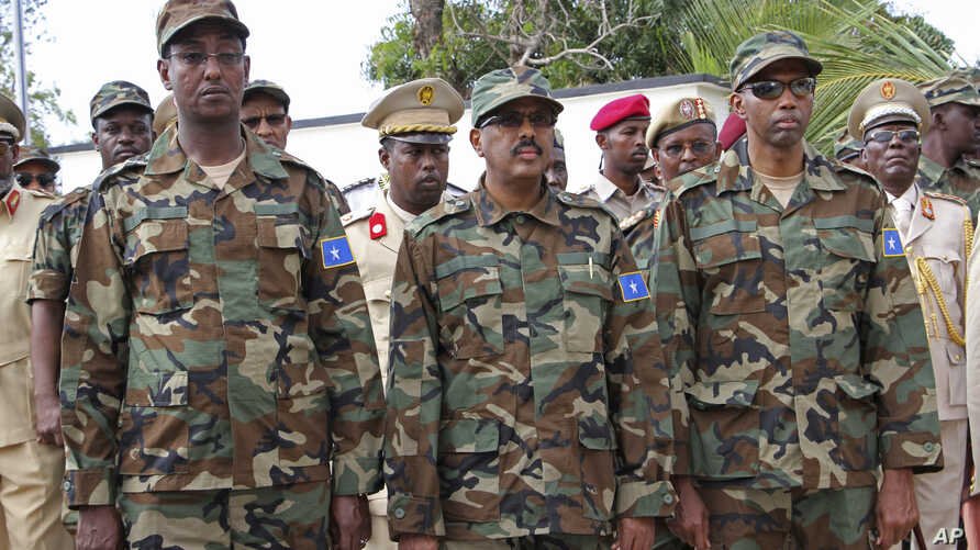 Somali President Mohamed Abdullahi Mohamed, center, Somalia Prime Minister Hassan Ali Khayre, right , and Defense Minister Abdirashid Abdulahi Mohamed watch a military unit during celebrations marking the 57th anniversary since Somali military was fo