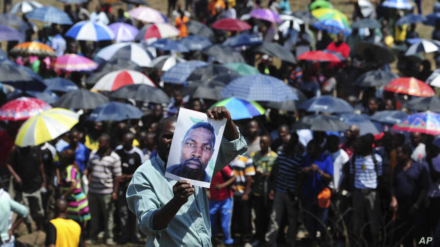 A man holds an image of an un-named alleged victim of the recent mining violence during a demonstration in Rustenburg, South Africa, October 6 2012.