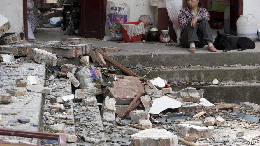 A woman looks over at her destroyed house in Gucheng village in Longmen county of southwestern China's Sichuan province, April 21, 2013.