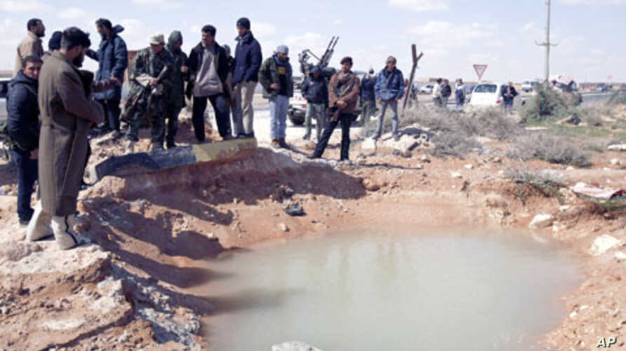 Anti-Gadhafi rebels survey the damage after an airstrike near the eastern city of Ras Lanuf, March 8, 2011