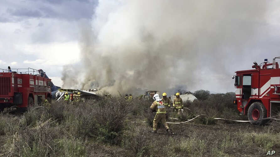 """Rescue workers and firefighters are seen at the site where an Aeromexico airliner has suffered an """"accident"""" in a field near the airport of Durango, Mexico, July 31, 2018."""
