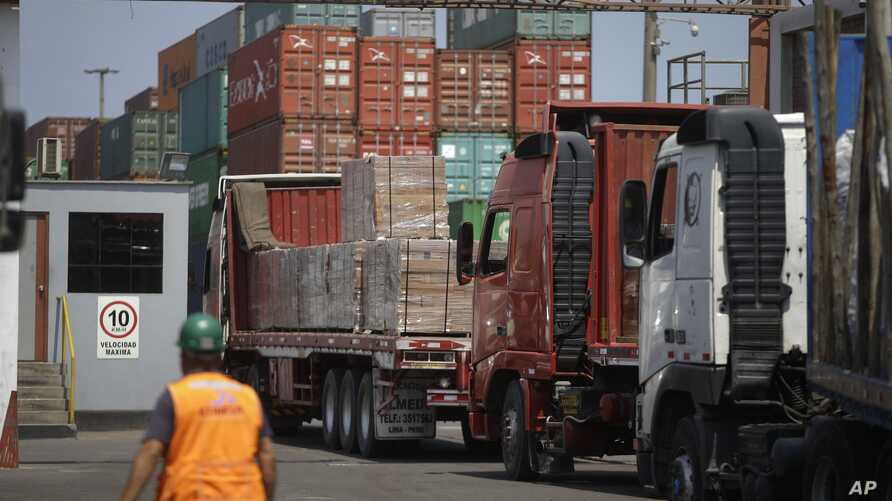 FILE - In this photo taken Feb. 20, 2017, a customs agent observes the arrival of trucks with wood from the Peruvian Amazon at the port of Callao, Peru.