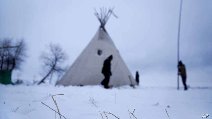 Snow lays on the ground as campers from Colorado set up a teepee at the Oceti Sakowin camp where people have gathered to protest the Dakota Access oil pipeline near Cannon Ball, N.D., Wednesday, Nov. 30, 2016.