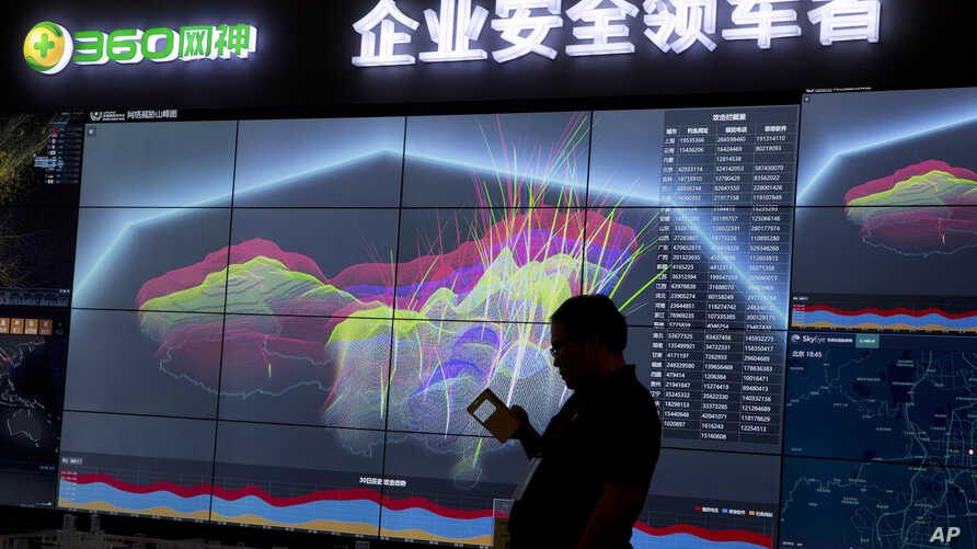 FILE - In this Aug. 16, 2016, photo, a worker is silhouetted against a computer display showing a live visualization of online phishing and fraudulent phone calls across China during the 4th China Internet Security Conference (ISC) in Beijing.