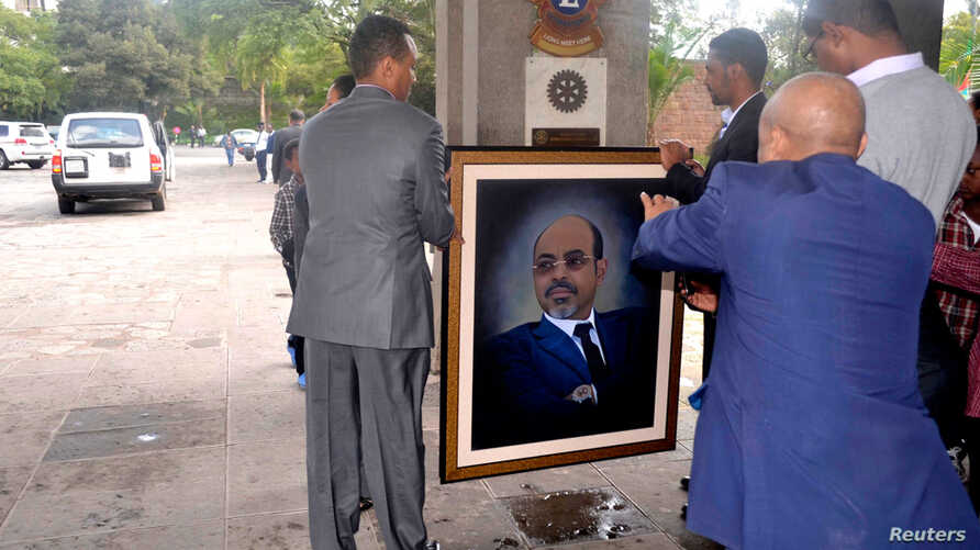Officials move a portrait of Meles Zenawi shortly after the announcement of his death in Addis Ababa August 21, 2012.