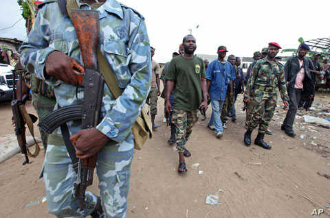 A man known as Commander Bauer, the chief of a group of pro-Ouattara fighters, walks with his men in northern Abidjan's Abobo district March 26, 2011