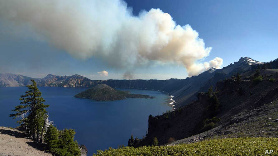 This photo provided by Inciweb.gov, shows smoke from Bybee Creek Wildfire drifting over Crater Lake, Oregon., July 30, 2016.