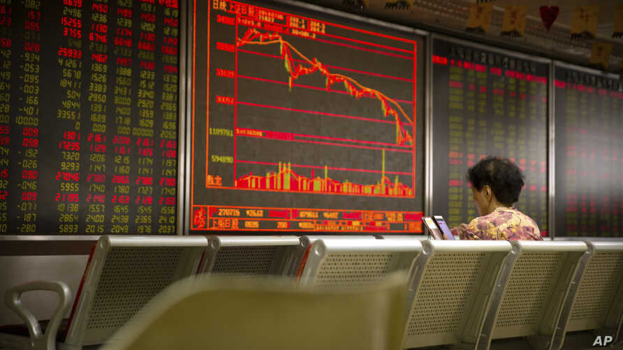 A Chinese investor uses her smartphone as she monitors stock prices at a brokerage house in Beijing, Friday, July 6, 2018. President Donald Trump made clear Thursday that U.S. tariffs against Chinese imports will take effect early Friday and that he'