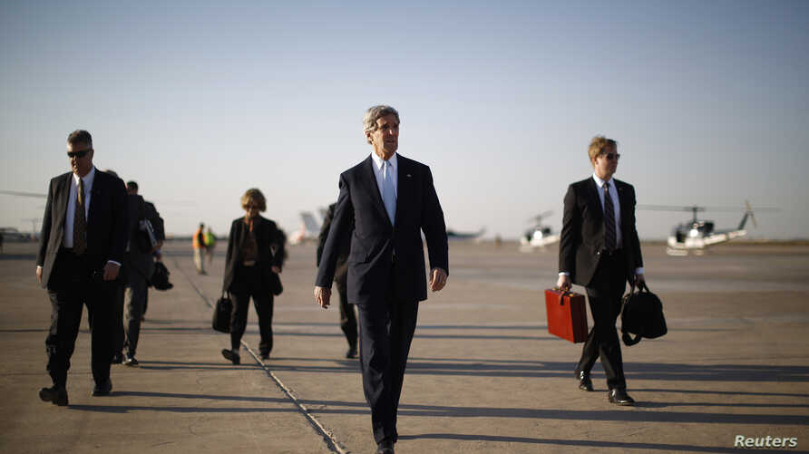 U.S. Secretary of State John Kerry (2nd R) walks across the tarmac of Baghdad International Airport as he prepares to board an aircraft out of the Iraqi capital, Mar. 24, 2013.