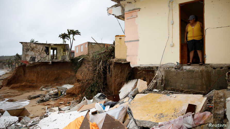 Yamary Morales looks at the damage at a neighbor's house after the area was hit by Hurricane Maria in Yabucoa, Puerto Rico Sept. 22, 2017.