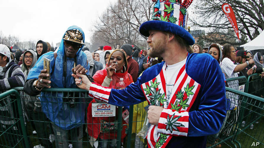 FILE -Patrick Bettis, of Glen Ellyn, Ill., a promoter of marijuana legalization, hands a joint to Larnell Rhea, of Denver, during the Mile High 420 Festival in Denver,April 20, 2018.