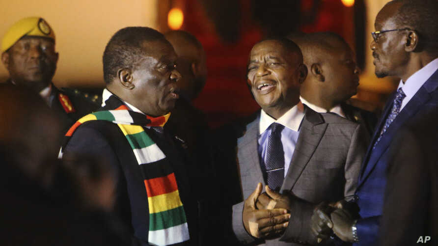 Zimbabwean President Emmerson Mnangagwa, left, arrives at Robert Mugabe International Airport in Harare, Zimbabwe, Monday, Jan. 21, 2019.