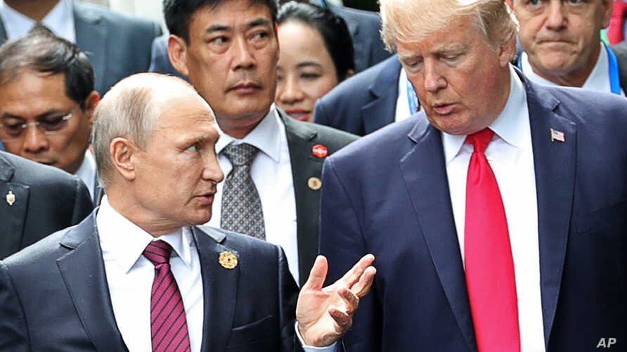 U.S. President Donald Trump, right, and Russia's President Vladimir Putin talk during the family photo session at the APEC Summit in Danang, Nov. 11, 2017.