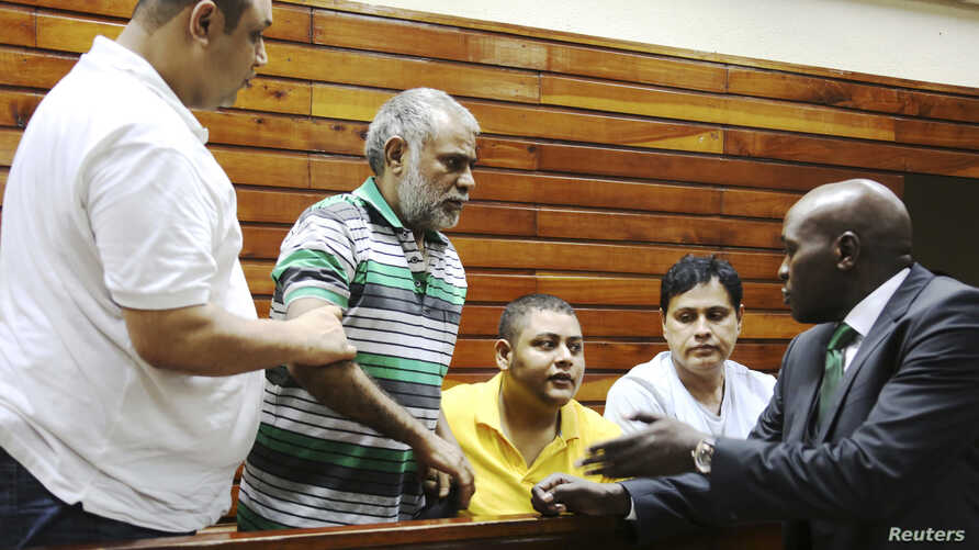 Baktash Akasha, from left, Gulam Hussein, Ibrahim Akasha and Vijaygiri Goswami are briefed by their lawyer Cliff Ombeta at Mombasa Law Courts during a court appearance on drug-related charges in Mombasa, Kenya, Feb. 17, 2015.