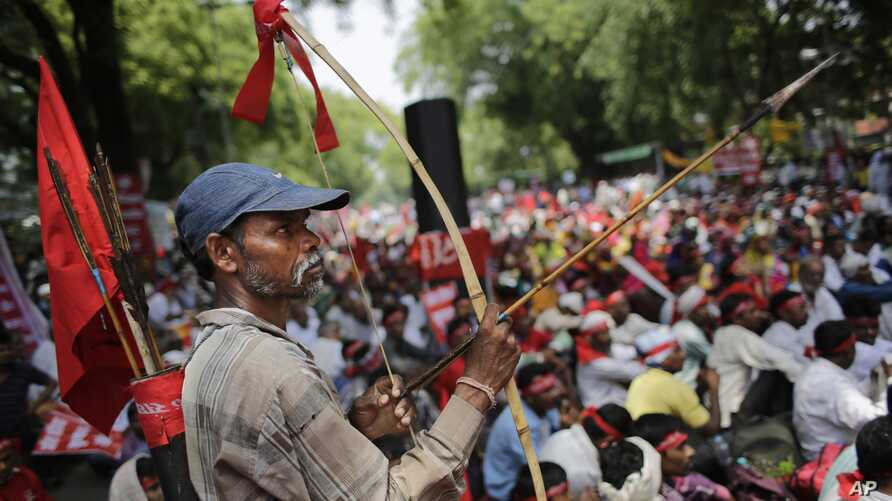 An Indian farmer holds a bow and an arrow as he attends a gathering near the Indian parliament for a protest against the Land Acquisition Bill, in New Delhi, India, May 5, 2015.