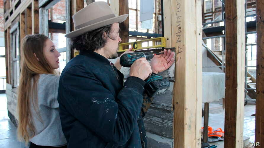 In this March 28, 2018 photo, artist Ryan Mendoza and his wife, Fabia Mendoza, put up siding, in Providence, R.I., on a house where Rosa Parks sought refuge after fleeing the South.