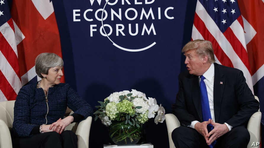 FILE - A Thursday, Jan. 25, 2018 file photo of US President Donald Trump meeting with British Prime Minister Theresa May at the World Economic Forum in Davos, Switzerland. President Donald Trump has wished Prince Harry and fiancee Meghan Markle well ...