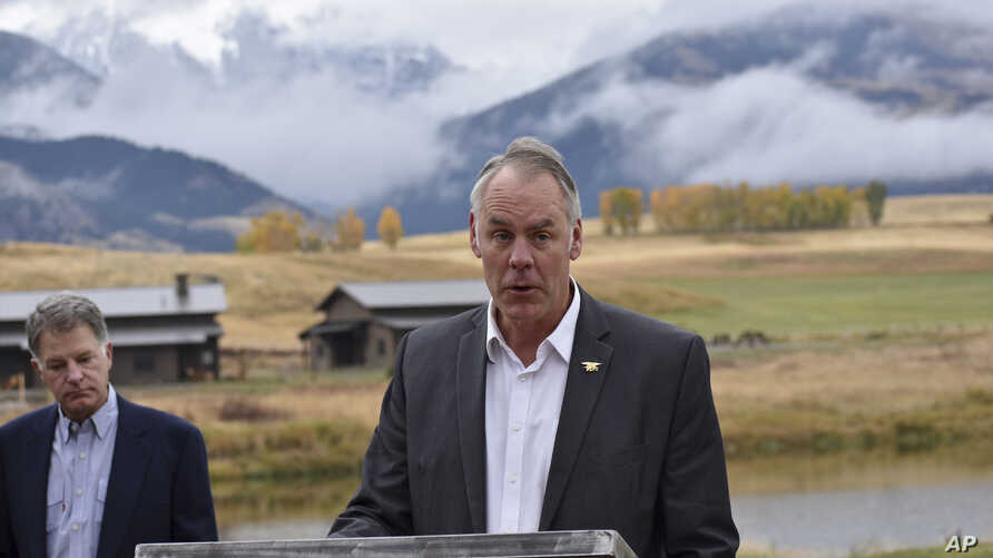 FILE - U.S. Interior Secretary Ryan Zinke announces a ban on mining claims north of Yellowstone National Park as K.C. Walsh, left, president of Simms Fishing Products, listens near Emigrant, Mont., Oct. 8, 2018.