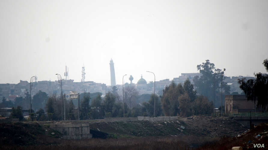 Iraqi soldiers say the tower in the distance is IS's main mosque in western Mosul and sniper fire regularly lands across the river aimed at them on Feb. 12, 2017 in Mosul, Iraq. (H.Murdock/VOA)