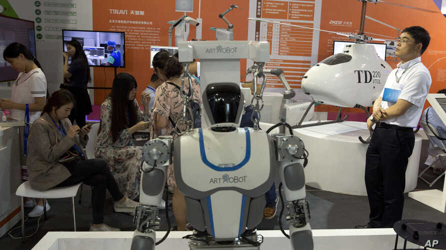 FILE - Visitors to the 21st China Beijing International High-tech Expo look at robots and helicopter drone displayed in Beijing, China, May 17, 2018.
