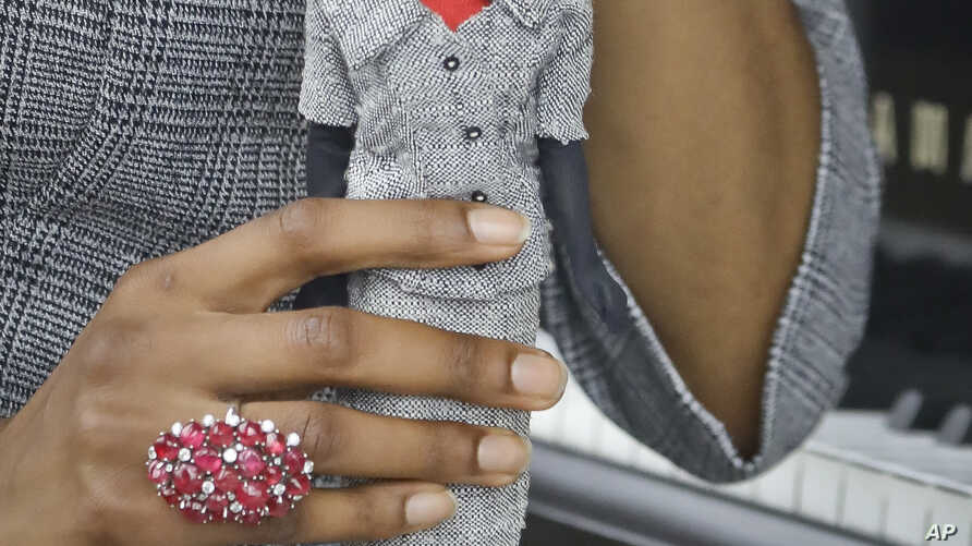 In this Nov. 5, 2018 photo, model Tiffany Hendrix holds a Barbie doll while wearing a matching outfit by designer Katie Echeverry in New York.