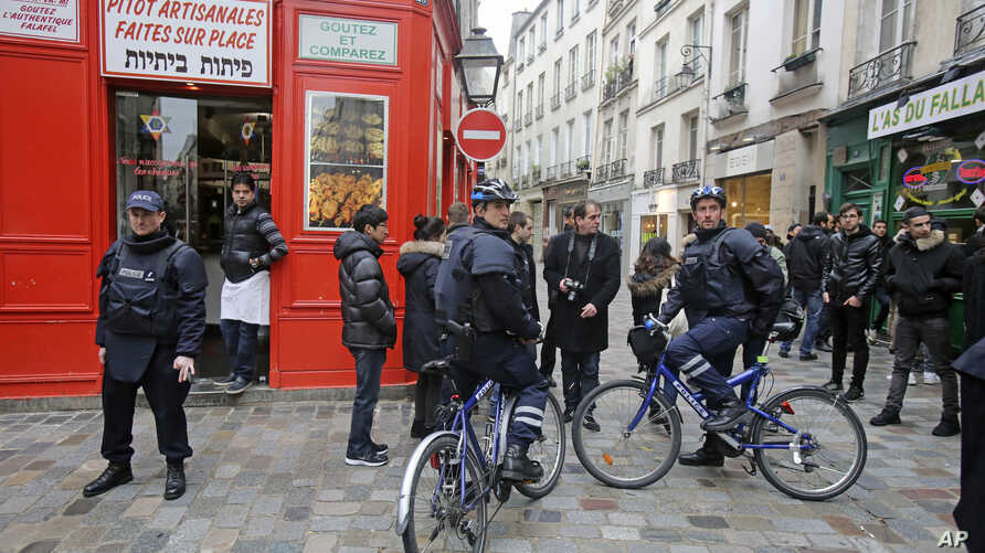Police officers on bicycle patrol Rue des Rosiers street, in the heart of the Paris Jewish quarter, Monday Jan. 12, 2015. France on Monday ordered 10,000 troops into the streets to protect sensitive sites after three days of bloodshed and terror, ami...