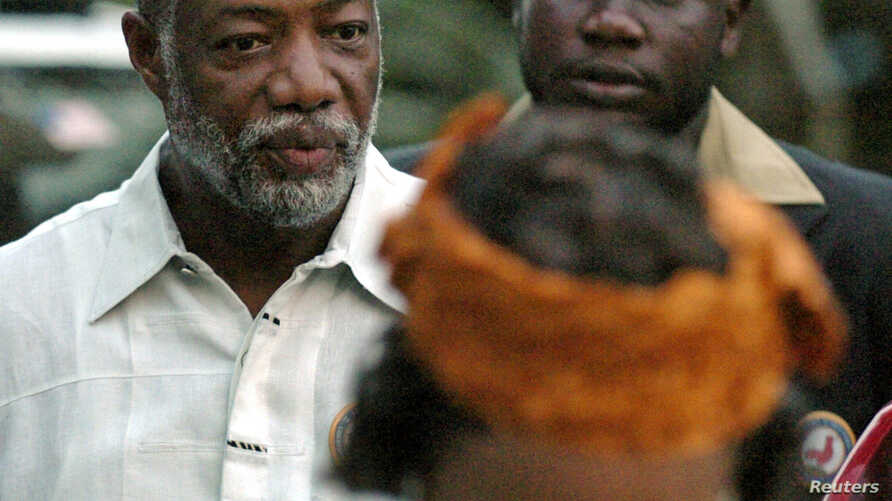 FILE - Varney Sherman (L) and his wife Joyce (front) arrive for a prayer service on the last night of election campaigning in Monrovia, 2005.