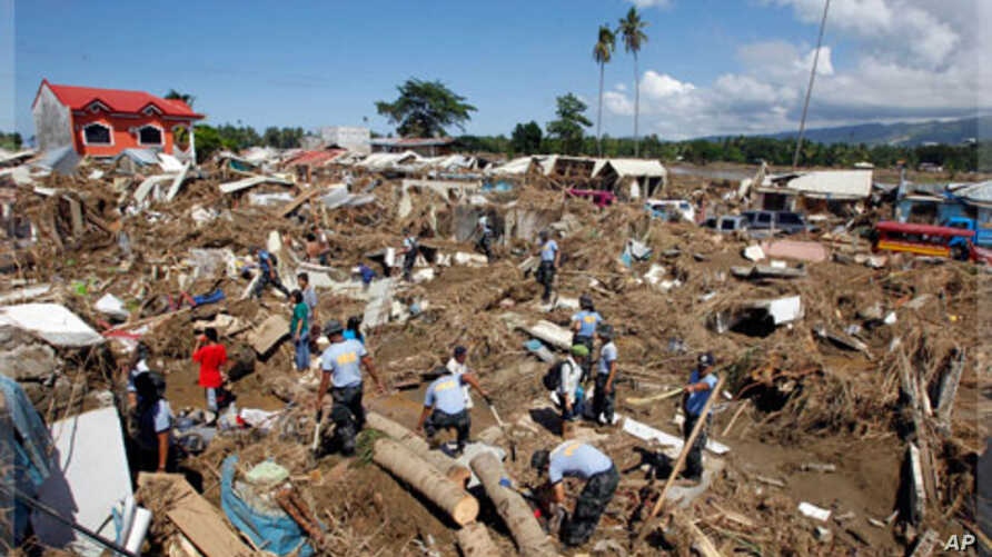 Policemen search for missing Typhoon Washi victims in a subdivision in Iligan city, southern Philippines. Disaster agencies on Monday rushed to deliver body bags, food, water, and medicine to crowded evacuation centers in the southern Philippines as