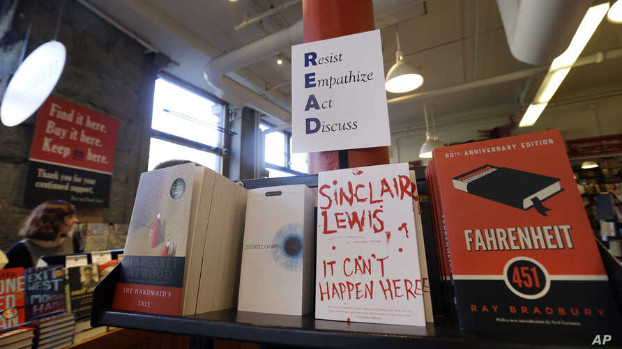 Books are displayed under a sign at the Harvard Book Store, March 9, 2017, in Cambridge, Mass. Readers have been flocking to classic works of dystopian fiction in the first months of Donald Trump's presidency.