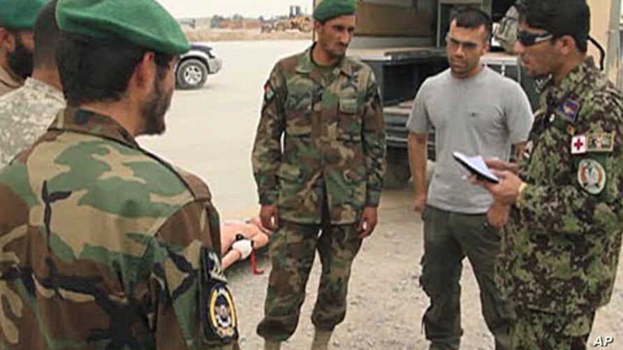 Afghan Air Force Sergeant Hayatullah Bahar Jawazjani, far right, comunicates with his compatriots, Aug 2010. He has been working with US military personnel for the past six months and has taken on a leadership role.