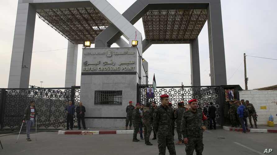FILE - Hamas security officers stand guard in front of the main gate of the Rafah border crossing while passengers cross the border to the Egyptian side, in Rafah, Gaza Strip, Nov. 18, 2017.