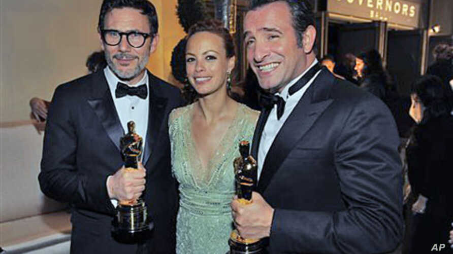 From left, Michel Hazanavicius with the award for best director for 'The Artist,' Berenice Bejo and Jean Dujardin with the award for best actor in a leading role for 'The Artist' at the Governors Ball following the 84th Academy Awards, in the Hollywo