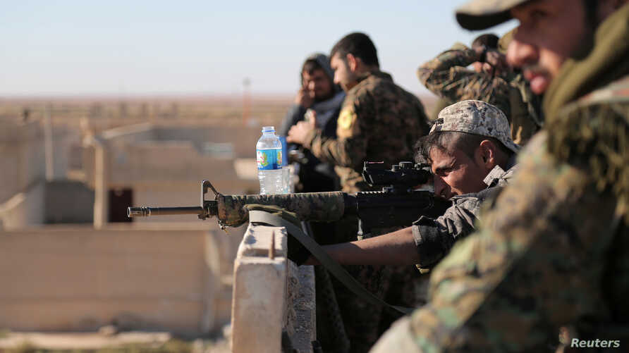 A Syrian Democratic Forces fighter looks through the scope of his weapon in Tal Samin village, north of Raqqa, Syria, Nov. 19, 2016.