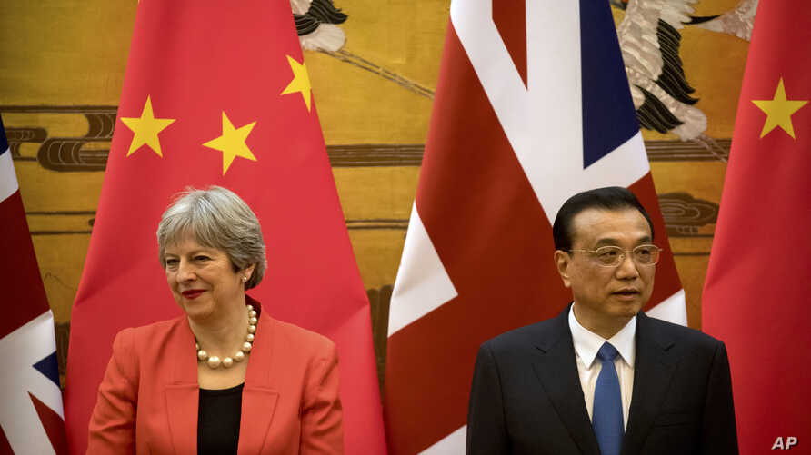 British Prime Minister Theresa May, left, and Chinese Premier Li Keqiang attend a signing ceremony at the Great Hall of the People in Beijing, Wednesday, Jan. 31, 2018.