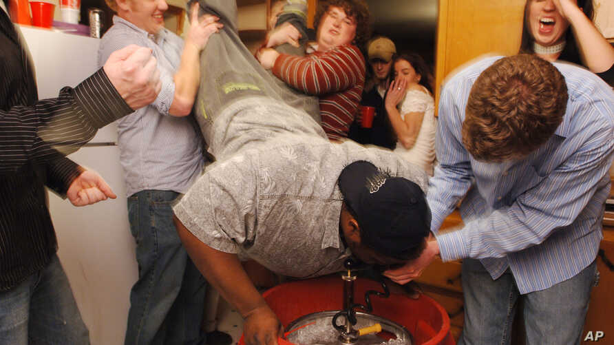 """FILE - A student does a """"keg-stand"""" over a keg of beer in Columbia, Mo., Nov. 12, 2005."""