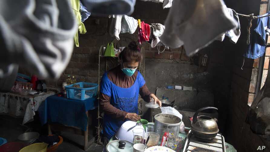 FILE - Jessica Vega, 40, who has drug-resistant tuberculosis, cooks in her home in the poor neighborhood of Carabayllo in Lima, Peru, Sept. 30, 2015. The world is making progress lifting people out of such extreme poverty.