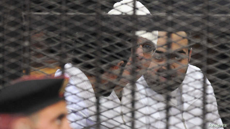 Political activists Ahmed Maher, Ahmed Douma (L) and Mohamed Adel (R) of the 6 April movement  look on from behind bars in Abdeen court in Cairo, December 22, 2013. Three leading Egyptian activists were sentenced to three years in prison each on Sund