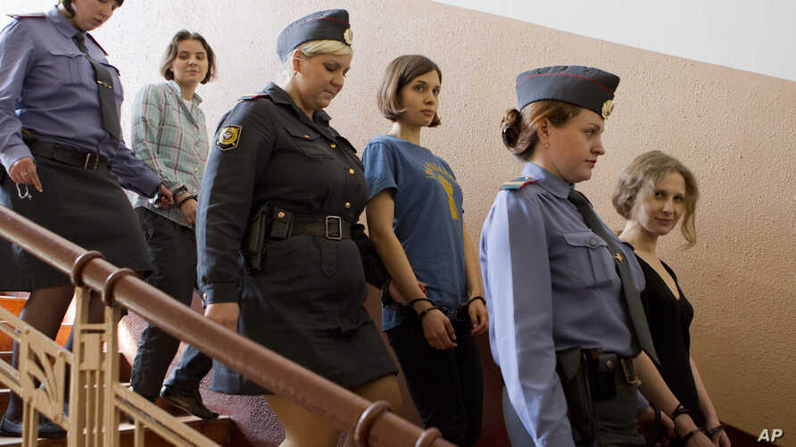 Feminist Russian punk group Pussy Riot members, Nadezhda Tolokonnikova, center, Maria Alekhina, front, and Yekaterina Samutsevich, are escorted to a glass cage at a court room in Moscow, Russia, August 17, 2012.