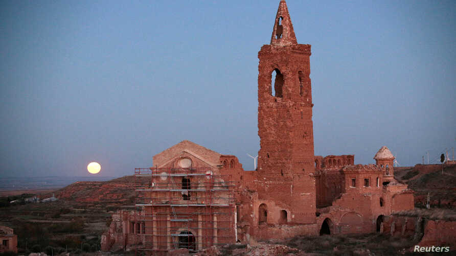 The moon rises behind the San Martin de Tours church in the old village of Belchite, in northern Spain, Nov. 14, 2016. The siege of Belchite was part of a Republican offensive in 1937 to capture Zaragoza from the Nationalists led by General Francisco