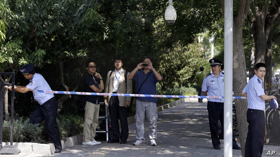 Chinese police officers set up a cordon for journalists outside the gate to the Japanese Embassy ahead of talks between Japan and North Korea in Beijing, Aug. 29, 2012.