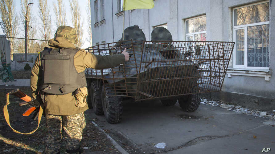 FILE - Ukrainian army soldiers park their APC as they guard a building in Volnovakha, eastern Ukraine, Oct. 26, 2014.