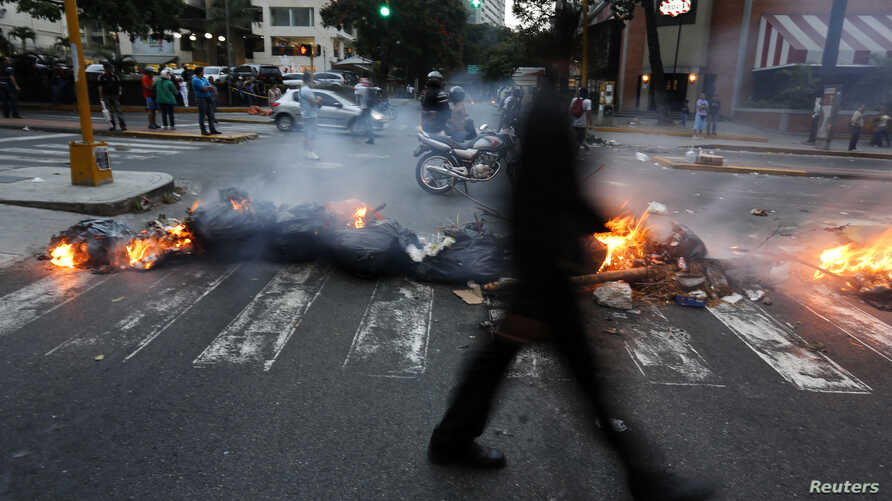 A man walks past a barricade set by anti-government protesters at Altamira square in Caracas, Venezuela, March 6, 2014.