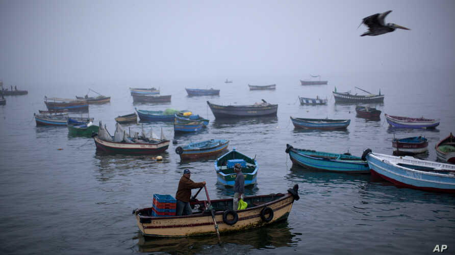 FILE - Fishermen navigate their boat out of the Chorrillo dock in the Pacific Ocean waters of Lima, Peru.