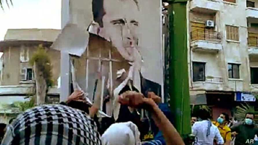 "A video downloaded from YouTube shows Syrian anti-government protesters tearing down a portrait of President Basahr al-Assad in Hama on April 29, 2011 during the ""Day of Rage"" demonstrations"