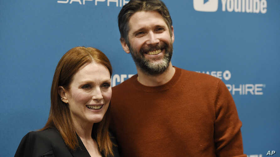 "Julianne Moore, left, a cast member in ""After the Wedding,"" poses with her husband, the film's writer/director Bart Freundlich, at the premiere of the film on the opening night of the 2019 Sundance Film Festival, Thursday, Jan. 24, 2019, in Park City"