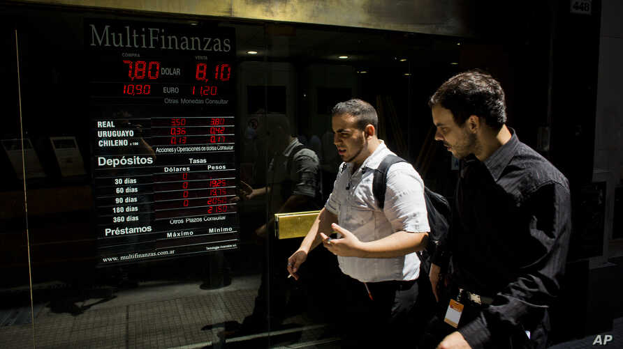 People walk by a sign indicating the exchange rate between the Argentine peso and the U.S. dollar in Buenos Aires, Argentina, Jan. 23, 2014.