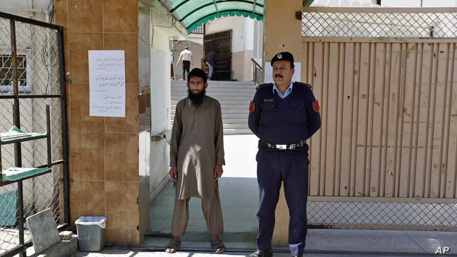 A Pakistani police officer stands guard with a worker of a religious group at the entrance to a mosque in Islamabad, Pakistan, March 6, 2019.