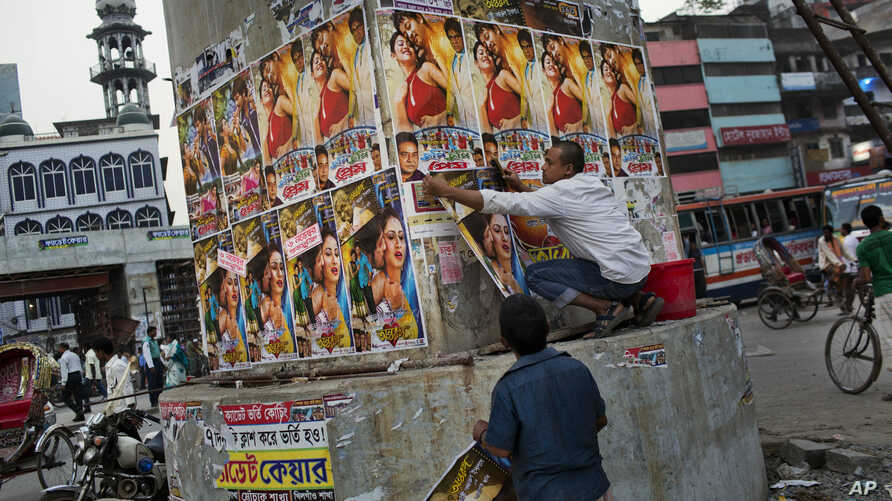 A Bangladeshi man glues movie posters in Dhaka, Bangladesh, Nov. 5, 2015. Fear is running high following months in which four bloggers and three other people have been killed.