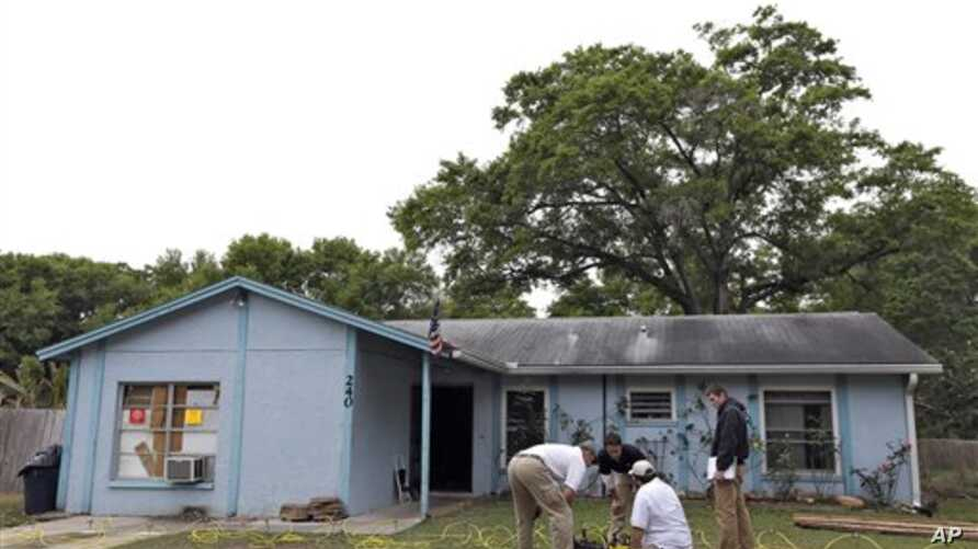 Engineers work in front of a home where sinkhole opened up underneath a bedroom and swallowed a man, in Seffner, Florida, March 1, 2013.